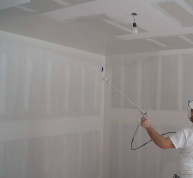 Painter spraying texture finish on new drywall